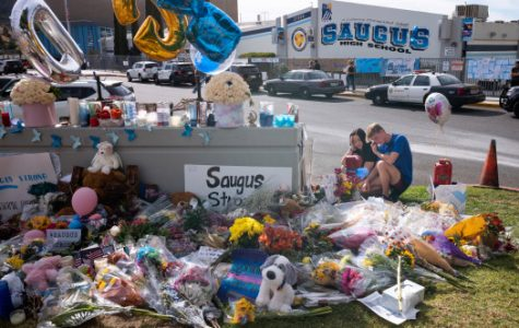 Saugus high students Katie Thanaet and Tyler Wilson look over items left at a memorial in front of the school Tuesday, November 19, 2019.  Students were allowed back on campus to collect their belongings left behind after the tragic shooting last Thursday.  Classes will resume at the high school on December 2nd. (Photo by David Crane, Los Angeles Daily News/SCNG)