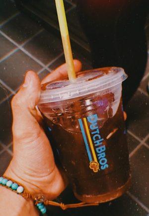 Holding a Dutch Bros Rebel drink.