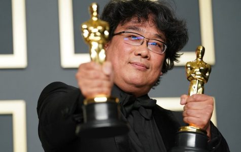 Bong Joon-Ho holding two Oscar awards for his film