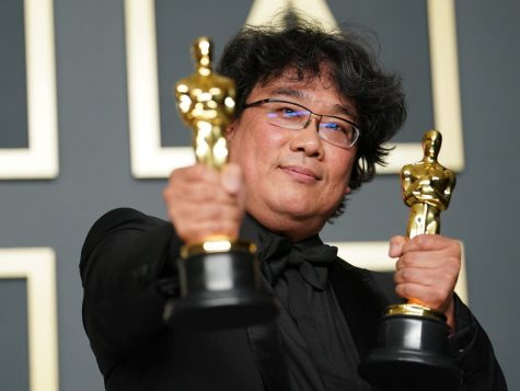"Bong Joon-Ho holding two Oscar awards for his film ""Parasite"""