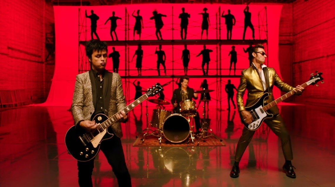 "Guitarist Billie Joe Armstrong (left), drummer Tré Cool, and bass guitarist Mike Dirnt (right) pictured in the music video for ""Father of All..."""