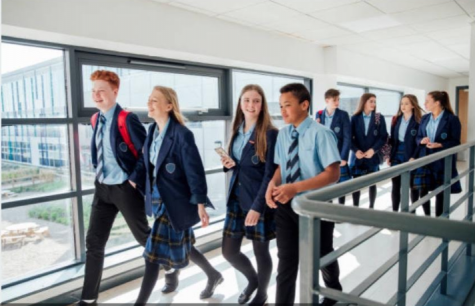 Students in uniforms walking through school hallways (Photo Credit- Pixabay)