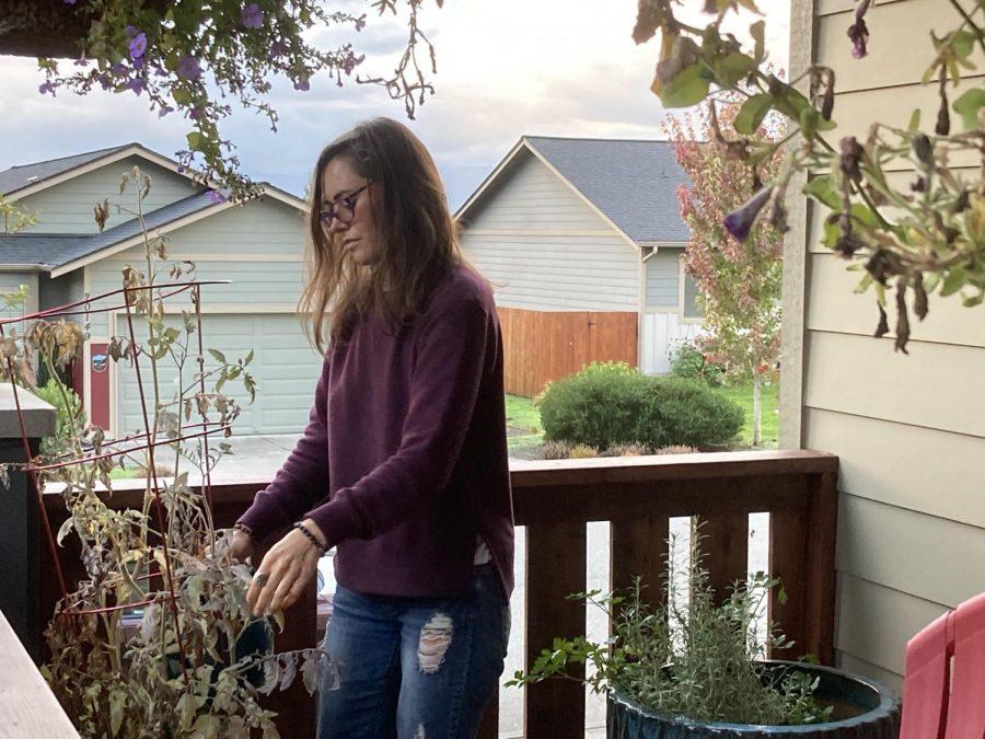 Rachel Sebastian waters the plants outside Lara Charters' home in Poulsbo Washington.