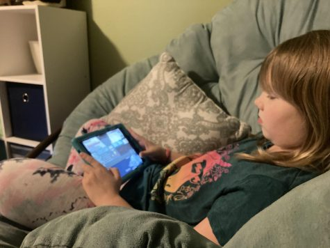 """Third grade student of Cougar Valley Elementary school plays """"Among Us."""" on her tablet from the comfort of her own home."""