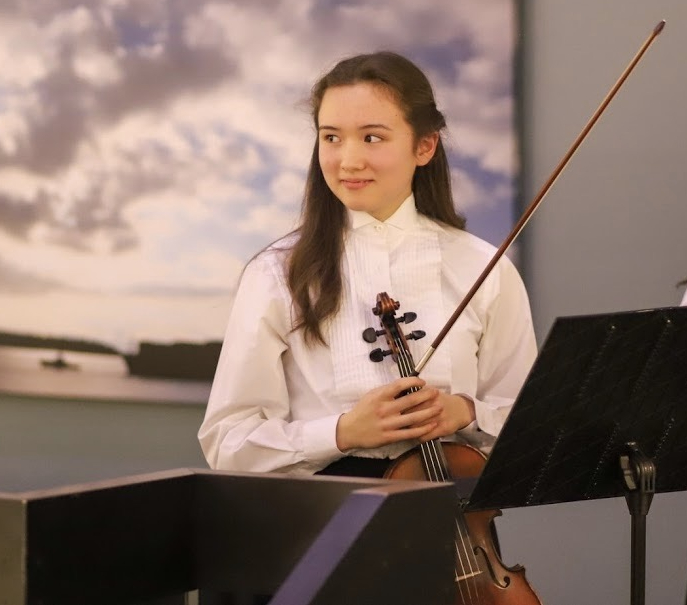 Tia-Jane Fowler holds her violin at a performance.